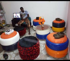 Alioune Doucouré dans un salon équipé de meubles fabriqués par lui meme à partir de pneus usagés